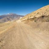 Strada non asfaltata attraverso i terreni incolti aridi della montagna Fotografia Stock