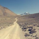 Strada non asfaltata attraverso i terreni incolti aridi della montagna Fotografie Stock Libere da Diritti