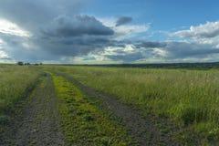 Strada non asfaltata attraverso il campo sui precedenti delle nuvole di pioggia fotografie stock libere da diritti