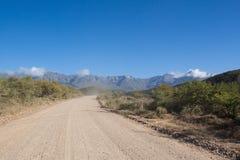 Strada non asfaltata che conduce sopra il passaggio di alta montagna di giorno Fotografia Stock
