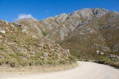 Strada non asfaltata che conduce sopra il passaggio di alta montagna di giorno Fotografia Stock Libera da Diritti