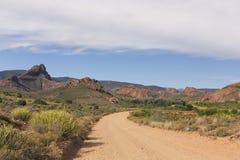 Strada non asfaltata che conduce sopra il passo di montagna di giorno Fotografie Stock