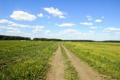 Strada non asfaltata del campo Cielo blu e nubi Fotografie Stock