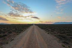 Strada non asfaltata diritta lunga al tramonto nel parco nazionale di Camdeboo Fotografia Stock Libera da Diritti