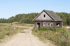 Strada non asfaltata e casa di legno abbandonata Fotografie Stock