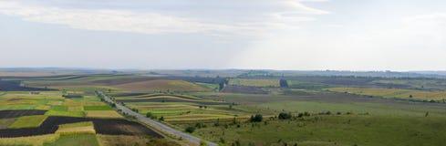 Strada panoramica attraverso i campi agricoli Immagine Stock