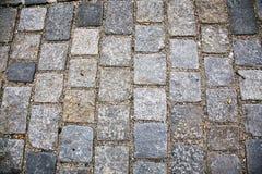 Strada pavimentata con le pietre per lastricati Cobbles il fondo fotografia stock libera da diritti