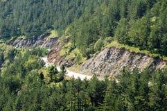 Strada perforata vicino nelle montagne e nelle foreste della Serbia Immagine Stock