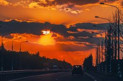 Strada principale con le automobili che viaggiano sul tramonto Linea di orizzonte con il sole e le nuvole di tempesta viaggi Fuoc immagine stock libera da diritti