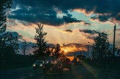 Strada principale con le automobili che viaggiano sul tramonto Linea di orizzonte con il sole e le nuvole di tempesta viaggi Fuoc immagini stock libere da diritti