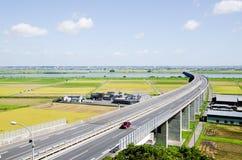 Strada principale e Paddy Field nella stagione Giappone del raccolto Fotografia Stock