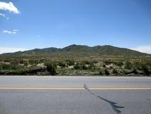 Strada principale, montagna e cielo blu occidentali immagine stock libera da diritti