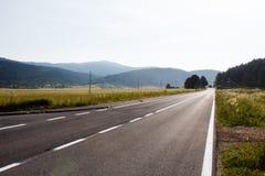Strada principale scura dell'asfalto circondata con le colonne del campo di verde di foresta e di energia elettrica in montagne i Fotografie Stock Libere da Diritti
