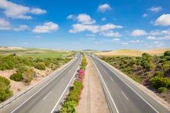 Strada principale senza fine sola nel bello paesaggio di Cadice immagine stock