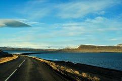 Strada principale in un paesaggio con le montagne e laghi in Islanda Fotografia Stock