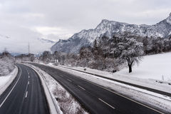 Strada principale vuota nelle alpi svizzere nell'inverno Immagine Stock