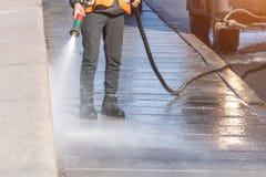 Strada privata di pulizia del lavoratore con la rondella ad alta pressione della benzina che spruzza la sporcizia, argine del gra fotografia stock