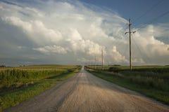 Strada rurale con le nuvole drammatiche nel Minnesota del sud al tramonto Immagini Stock Libere da Diritti