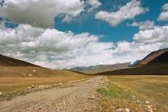 Strada rurale fra le montagne dell'Asia centrale con le grandi nuvole nel cielo per un momento prima di un temporale Fotografie Stock