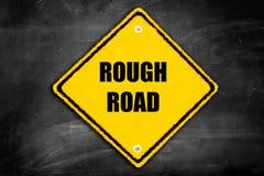 Strada ruvida scritta sul segno di cautela Immagini Stock