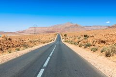Strada senza fine in Sahara Desert con cielo blu, Marocco Africa fotografie stock libere da diritti