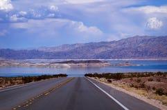 Strada senza fine in un lago con le montagne Immagine Stock Libera da Diritti