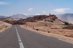 Strada sola ad un piccolo villaggio nel deserto del Marocco fotografia stock