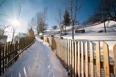 Strada stretta coperta da neve alla campagna Paesaggio di inverno con gli alberi nevicati, la strada ed il recinto di legno Giorn Fotografie Stock