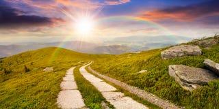 Strada su un pendio di collina vicino al picco di montagna al tramonto Fotografie Stock Libere da Diritti