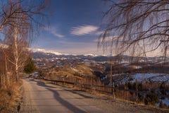 strada sul fianco di una montagna che trascura i villaggi di alta montagna nei precedenti le montagne innevate sull'orizzonte rom Immagine Stock