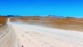 Strada a terra attraverso il deserto fotografia stock libera da diritti