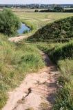 Strada a terra attraverso le colline al fiume Immagine Stock