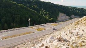 Strada tortuosa di panorama attraverso il legno nelle montagne Vista della strada della montagna da sopra Vista dal stock footage