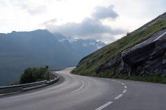 Strada tortuosa e belle nuvole alte nelle montagne Fotografia Stock