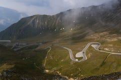 Strada tortuosa e belle nuvole alte nelle montagne Immagini Stock Libere da Diritti