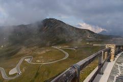 Strada tortuosa e belle nuvole alte nelle montagne Immagini Stock