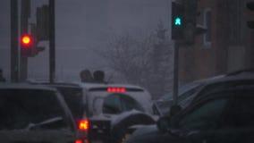 Strada trasversale della città con la bufera di neve della neve di inverno determinare le automobili, i semafori rossi e verdi di archivi video