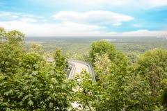 Strada urbana attraverso le colline verdi Immagini Stock
