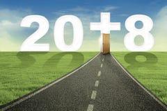 Strada verso il numero 2018 con un simbolo trasversale Fotografia Stock