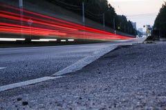 Strada vuota alla notte Le luci dell'automobile di passaggio, esposizione lunga fotografia stock libera da diritti
