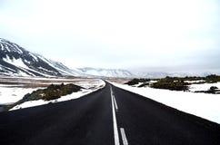 Strada vuota attraverso neve e le montagne Immagini Stock Libere da Diritti
