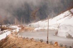 Strada vuota che conduce attraverso la campagna, la neve & la nebbia sceniche alla montagna di Grossglockner, Austria Fotografia Stock