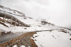 Strada vuota che conduce attraverso la campagna, la neve & la nebbia sceniche alla montagna di Grossglockner, Austria Fotografie Stock Libere da Diritti