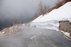 Strada vuota che conduce attraverso la campagna, la neve & la nebbia sceniche alla montagna di Grossglockner, Austria Immagini Stock