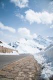 Strada vuota che conduce attraverso la campagna, la neve & la nebbia sceniche alla montagna di Grossglockner, Austria Immagini Stock Libere da Diritti