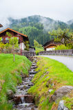 Strada vuota che conduce attraverso la campagna, la neve & la nebbia sceniche alla montagna di Grossglockner, Austria Immagine Stock Libera da Diritti