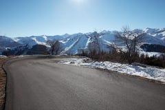 Strada vuota della montagna con la vista delle alpi in un giorno soleggiato Fotografia Stock