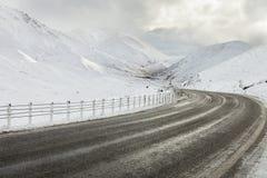 Strada vuota della montagna un giorno di inverno nuvoloso. Fotografie Stock Libere da Diritti