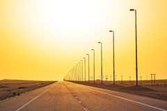 Strada vuota nel deserto al tramonto Fotografia Stock