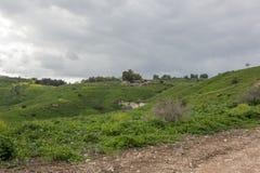 Strade non asfaltate fra le montagne piene di erba verde fotografia stock